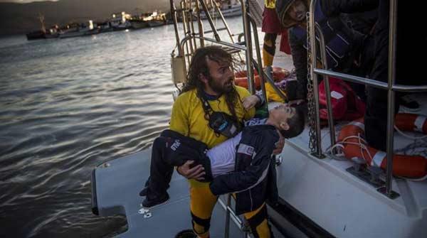 На фото: Испанский доброволец Оскар Камп спасает сирийского ребенка в Эгейском море